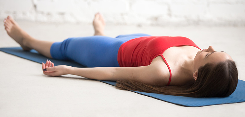 woman-laying-on-a-yoga-mat